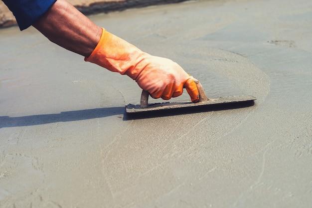 Nahaufnahmehandarbeiter, der betonpflasterung für mischungszement an der baustelle nivelliert Premium Fotos
