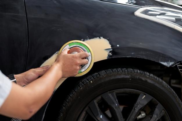 Nahaufnahmehandmechanikerarbeitskraft, die polierautokörper versandet und für das malen am stationsservice sich vorbereitet Premium Fotos