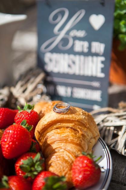 Nahaufnahmehochzeitsringe liegen auf frischen hörnchen, dekorationen an einem hochzeitspicknick mit erdbeeren. Premium Fotos