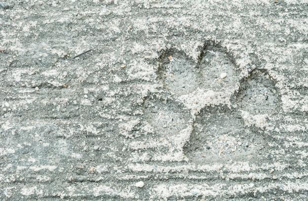 Nahaufnahmehundeabdruck am schmutzigen zementboden-beschaffenheitshintergrund Premium Fotos