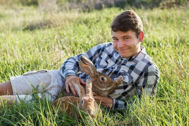 Nahaufnahmejunge, der kaninchen am bauernhof hält Kostenlose Fotos