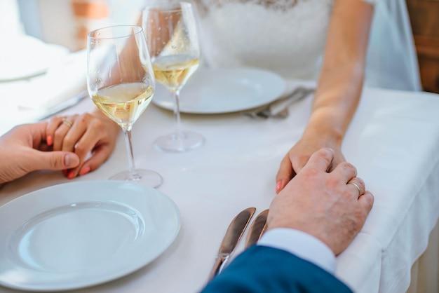Nahaufnahmejungvermählten halten sich hand an einem tisch im restaurant mit zwei gläsern wein Premium Fotos