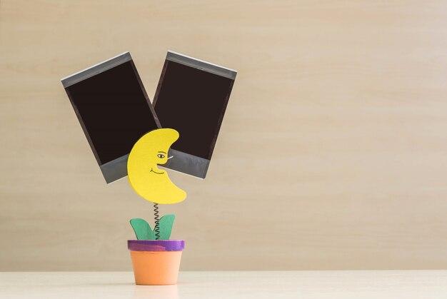 Nahaufnahmeklammerfoto in der gelben mondform im blumentopf mit schwarzem leerem film Premium Fotos