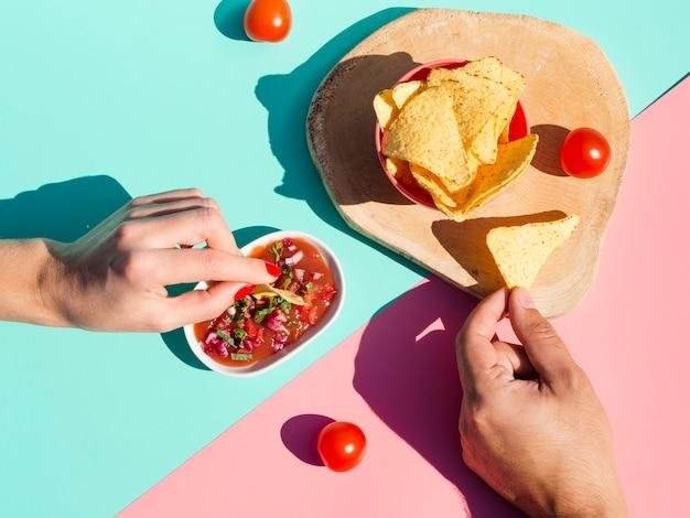 Nahaufnahmeleute mit soße und tortillachips Kostenlose Fotos