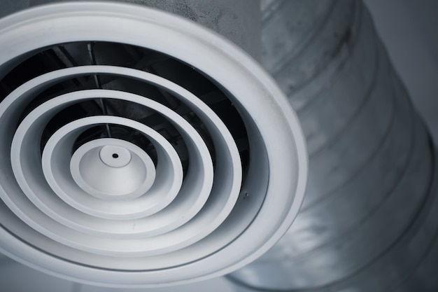 Nahaufnahmeluftlochgrill des innenluftkanals des abkühlenden klimaanlagenmetallrohres im gebäude. Premium Fotos