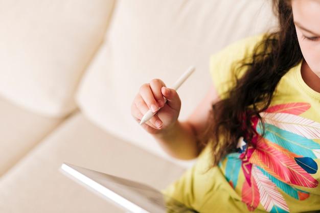 Nahaufnahmemädchen, das auf der couch mit tablette und stift sitzt Kostenlose Fotos