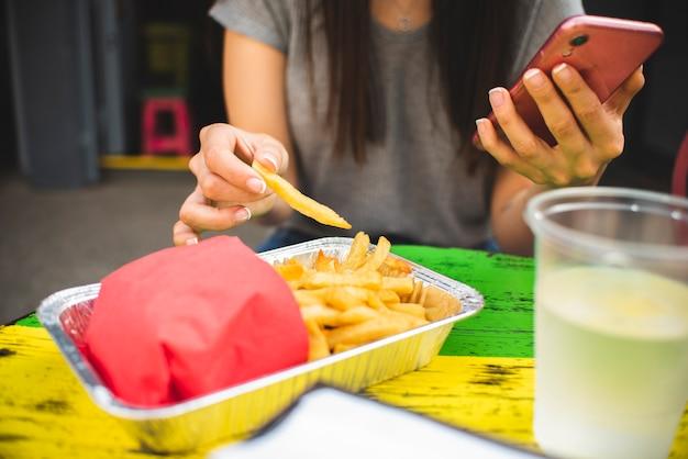 Nahaufnahmemädchen mit telefon fischrogen essend Kostenlose Fotos