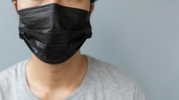 Nahaufnahmemänner, die eine maske tragen, um das coronavirus (covit-19) mit weichzeichner zu schützen Premium Fotos