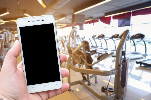 Nahaufnahmemänner verwenden hand, die smartphone unscharfe bilder der abstrakten unschärfe des defocused spors hält Premium Fotos