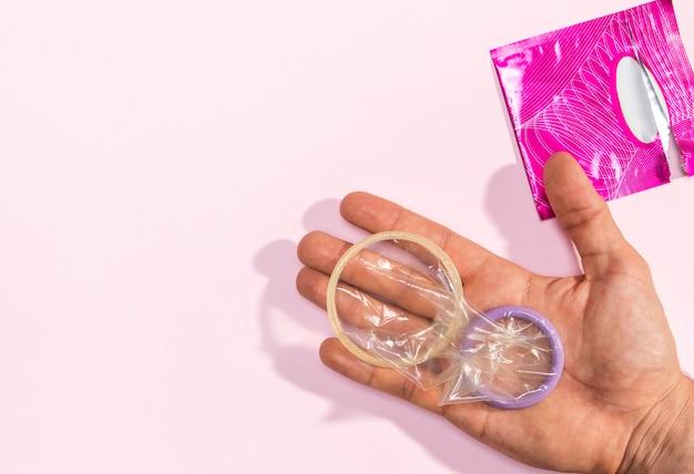 Nahaufnahmemann, der ausgepackte kondome hält Kostenlose Fotos