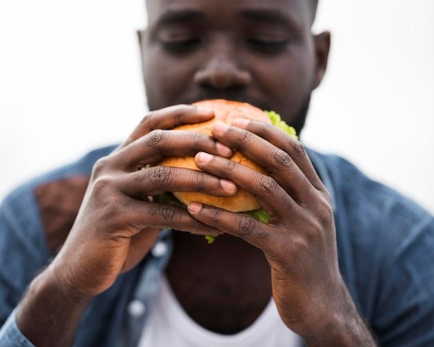 Nahaufnahmemann, der burger isst Kostenlose Fotos