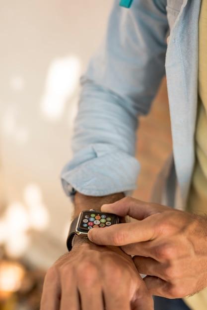 Nahaufnahmemann, der smartwatch überprüft Kostenlose Fotos