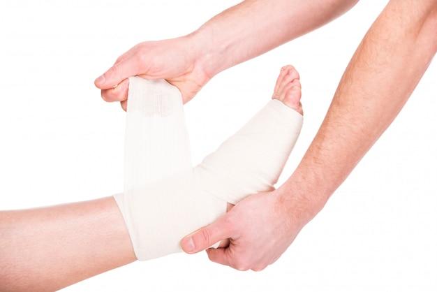 Nahaufnahmemann setzt verband auf verletzte füße. Premium Fotos