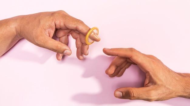 Nahaufnahmemannhände mit transparentem kondom Kostenlose Fotos