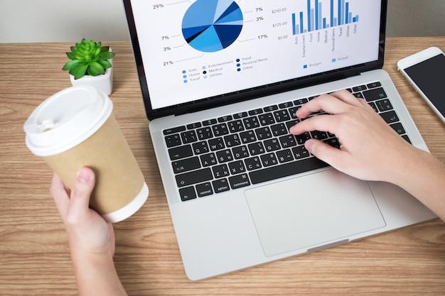 Nahaufnahmen von geschäftsleuten analysieren finanzdiagramme auf dem bildschirm und trinken gleichzeitig kaffee. Premium Fotos