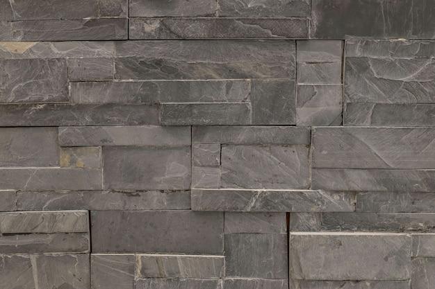 Nahaufnahmeoberflächen-ziegelsteinmuster am strukturierten hintergrund der alten schwarzen steinbacksteinmauer Premium Fotos