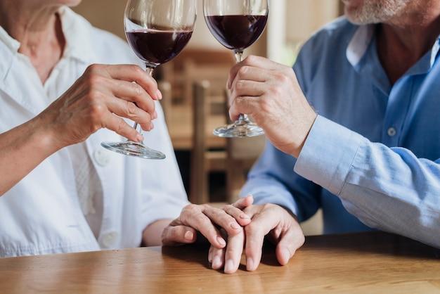 Nahaufnahmepaare, die einen toast am restaurant machen Kostenlose Fotos