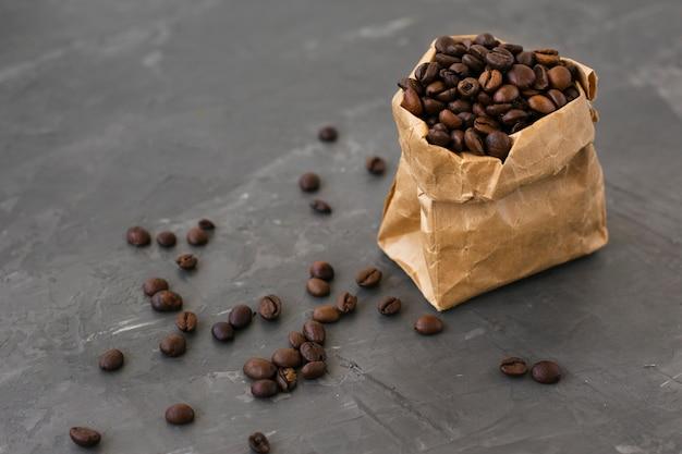 Nahaufnahmepapiertüte gefüllt mit kaffeebohnen Kostenlose Fotos
