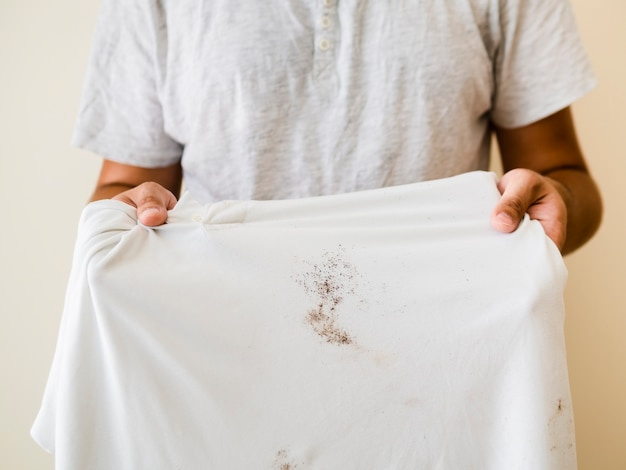 Nahaufnahmeperson, die beflecktes hemd zeigt Kostenlose Fotos