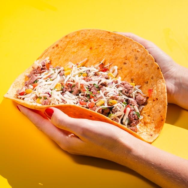 Nahaufnahmeperson, die entfalteten burrito hält Kostenlose Fotos