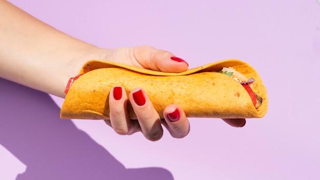 Nahaufnahmeperson mit burrito und purpurrotem hintergrund Kostenlose Fotos