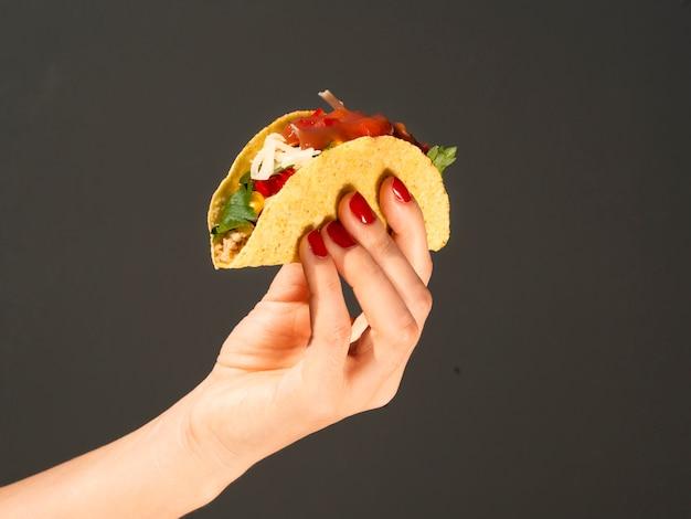 Nahaufnahmeperson mit taco und dunklem hintergrund Kostenlose Fotos
