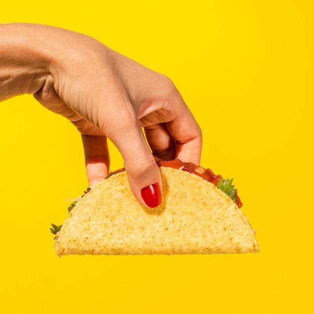 Nahaufnahmeperson mit taco und gelbem hintergrund Kostenlose Fotos