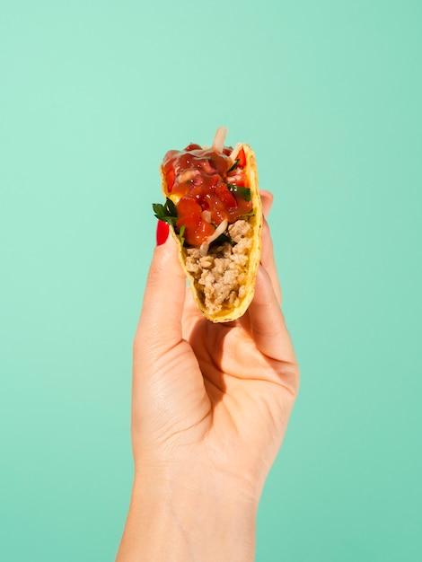 Nahaufnahmeperson mit taco und grünem hintergrund Kostenlose Fotos