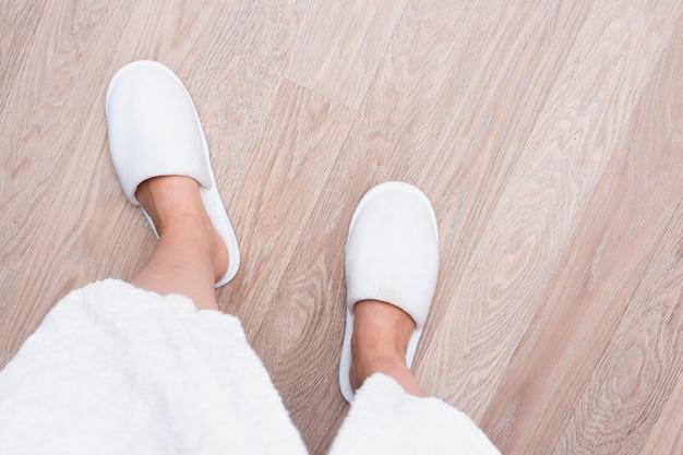 Nahaufnahmeperson mit weißen schuhen auf bretterboden Kostenlose Fotos