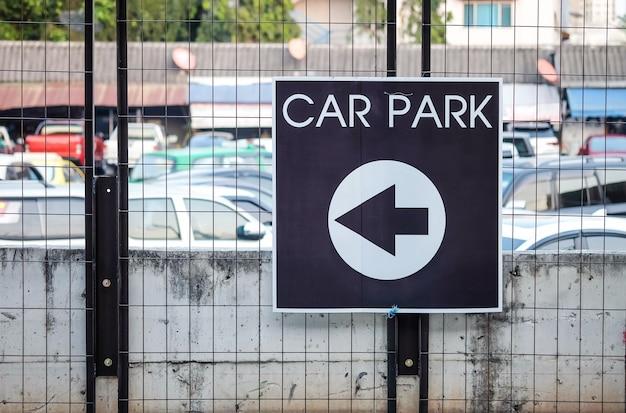 Nahaufnahmepfeilzeichen erklären die weise, parkplatz auf strukturiertem hintergrund des eisenzauns zu parken Premium Fotos