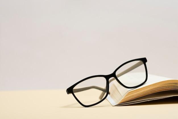 Nahaufnahmeplastikbrillen auf einem buch Kostenlose Fotos
