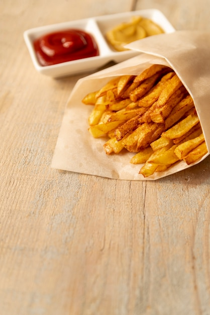Nahaufnahmepommes-frites mit hölzernem hintergrund Kostenlose Fotos