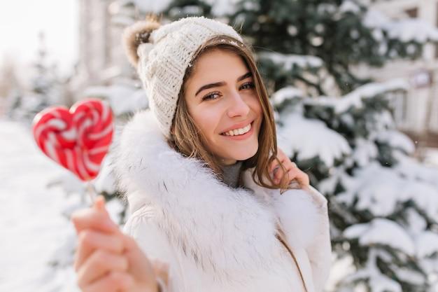 Nahaufnahmeporträt der bezaubernden dame im weißen mantel, der süßen lutscher hält. foto im freien der glückseligen blonden frau in der strickmütze, die neben baum am wintertag mit roter kandiszucker aufwirft. Kostenlose Fotos