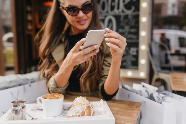 Nahaufnahmeporträt der frau mit gebräunter hauttextnachricht während des mittagessens im straßencafé Kostenlose Fotos