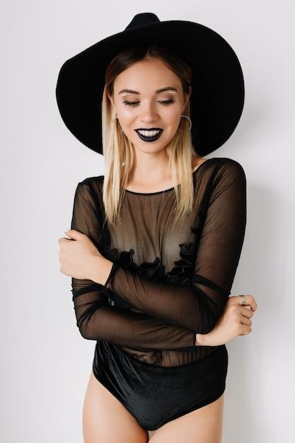 Nahaufnahmeporträt der herrlichen blonden jungen frau, die schwarzen hut und bodysuit trägt Kostenlose Fotos