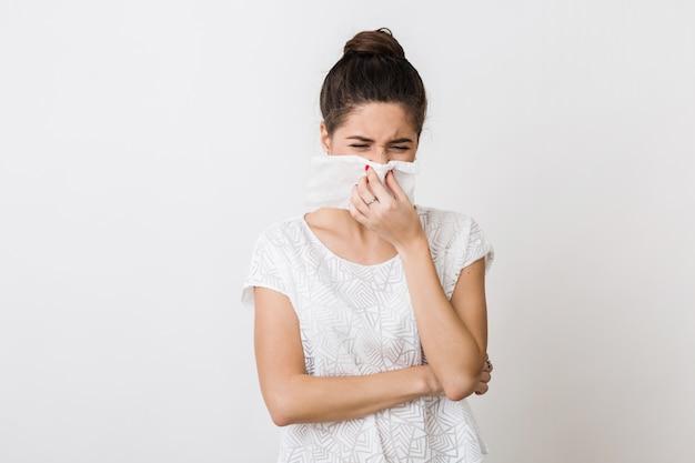 Nahaufnahmeporträt der hübschen frau, die ihre nase mit serviette putzt, sich erkältet, sich krank, isoliert, stirnrunzelnd fühlt Kostenlose Fotos