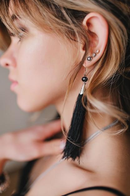 Nahaufnahmeporträt der hübschen frau mit dem lockigen haar, stilvolles schwarzes outfit. Kostenlose Fotos