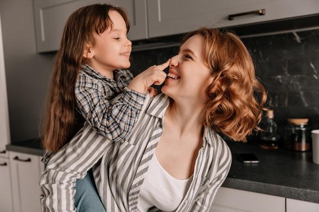 Nahaufnahmeporträt der lockigen jungen mutter und ihrer kleinen fröhlichen tochter in der küche. Kostenlose Fotos