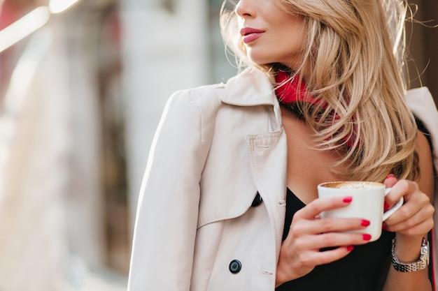 Nahaufnahmeporträt der raffinierten blonden frau im mantel, der weiße tasse mit getränk hält. charmante blonde frau, die an einem kalten tag kaffee trinkt und wegschaut. Kostenlose Fotos