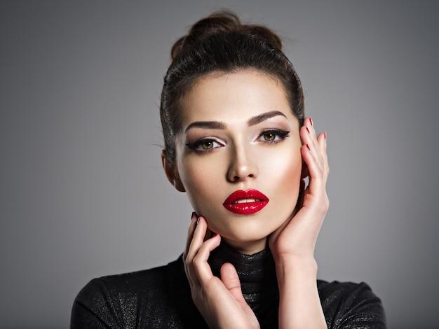 Nahaufnahmeporträt der schönen frau mit hellem make-up und roten nägeln. sexy junges erwachsenes mädchen mit rotem lippenstift. Kostenlose Fotos