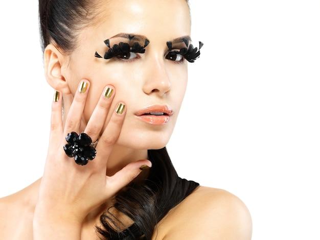 Nahaufnahmeporträt der schönen frau mit langem schwarzen falschen wimpernmake-up und goldenen nägeln. isoliert auf weißer wand Kostenlose Fotos