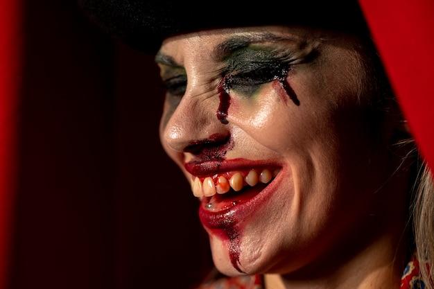 Nahaufnahmeporträt der seitlich clownfrau mit ihren augen schloss Kostenlose Fotos
