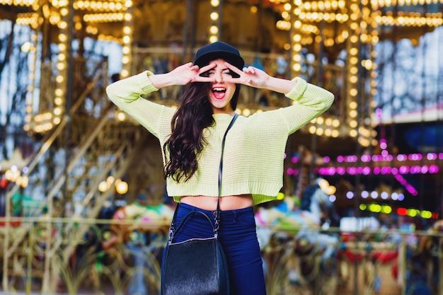 Nahaufnahmeporträt der sexy ausgefallenen stilvollen frau haben spaß und lächeln auf attraktionen. trägt einen trendigen schwarzen hut mit hipster-beute und einen neonpullover. Kostenlose Fotos