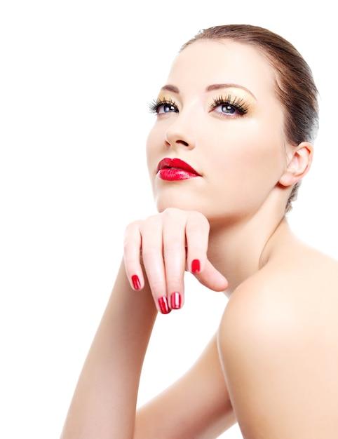 Nahaufnahmeporträt der sexy jungen kaukasischen jungen frau mit goldenem glamour-make-up und roter heller maniküre Kostenlose Fotos