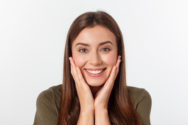 Nahaufnahmeporträt der überraschten schönheit ihren kopf in der verwunderung halten und mit offenem mund. über weiße wand Premium Fotos