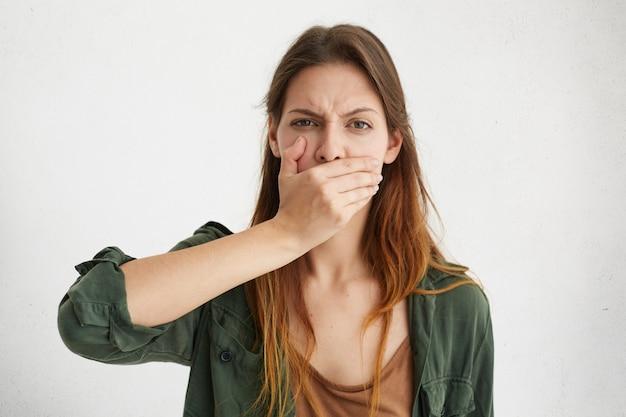 Nahaufnahmeporträt der verschlafenen hausfrau, die ihren mund mit der hand bedeckt, während gähnt, müde zu sein Kostenlose Fotos
