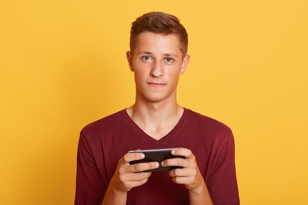 Nahaufnahmeporträt des attraktiven jungen studenten, der lässiges t-shirt trägt Kostenlose Fotos