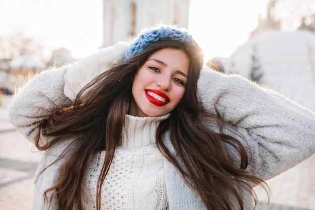 Nahaufnahmeporträt des fröhlichen mädchens mit dem langen schwarzen haar, das im wintermorgen auf unschärfestadt aufwirft. brünette dame in der blauen baskenmütze genießt fotoshooting am kalten tag. Kostenlose Fotos