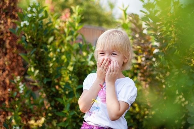 Nahaufnahmeporträt des glücklichen kleinen blobde mädchens im volksschulalter draußen im grünen park Premium Fotos
