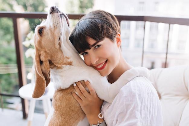 Nahaufnahmeporträt des glückseligen mädchens mit den grauen augen, die mit glücklichem lächeln aufwerfen, während ihr beagle-hund nach oben schaut Kostenlose Fotos